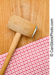 Meat tenderizer on wooden kitchen table, heckered...