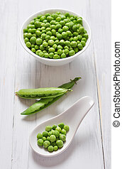 Green peas in ceramic bowl on white wooden background