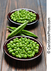 Green peas in ceramic bowl on wooden background