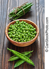 Green peas in ceramic plate on wooden background