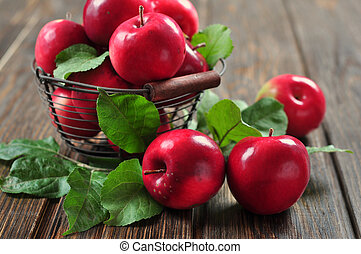 Apples in metal basket on wooden background