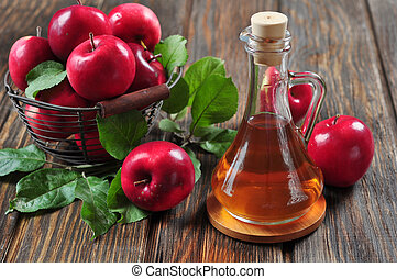 Apple cider vinegar in glass bottle and basket with fresh...