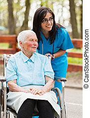 Visitors arriving - Elderly lady and nurse looking at the...