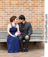 Lovers looking at each other while sitting on bench