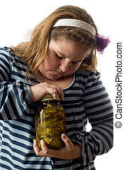 Child Opening Jar - Closeup of a young girl trying to open a...