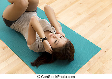 Sit ups - An Asian lady doing her sit ups exercise in a gym.