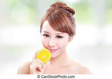 Beautiful woman face with juicy orange, green background,...