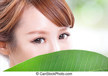 beautiful woman face portrait with green leaf - close up of...