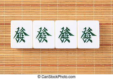 rich and good luck - four mahjong tiles on the bamboo mat,...