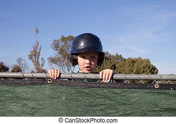 Baseball Player Peeking Over the Dug Out - A young boy...