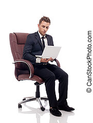 Handsome businessman sitting in chair with laptop