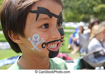 Boy with Pirate Face Paint - Side View - A young boy with...