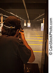 Man at the Shooting Range - A man taking aim at a paper...