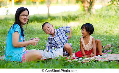 Happy mother with her daughter and son in the park