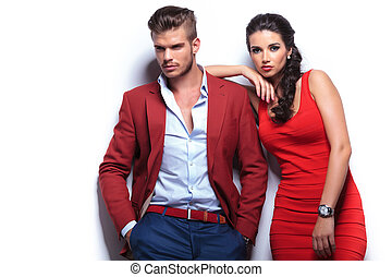 young fashion man and woman against white wall, posing for...