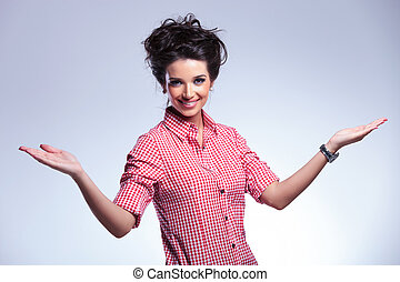 young casual woman welcoming you on a gray background