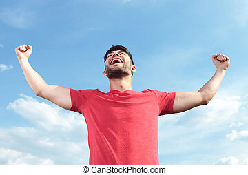 casual man shouting victorious - casual young man outdoor...