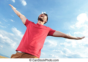 casual man screaming at the sky - casual young man outdoor...