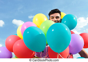 casual man surrounded by baloons