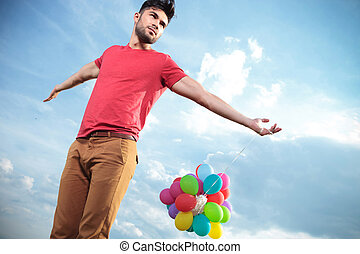 casual man with balloons looks to his side - casual young...
