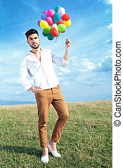 casual man with balloons and hand in pocket - full length...