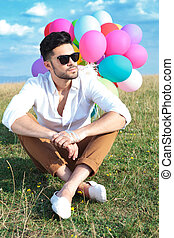seated casual man with balloons looks away - casual young...