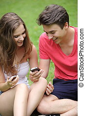 Couple of teenagers looking at their mobile phones - Happy...