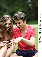Teenage couple reading a text message