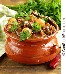 Beef stew with vegetables and herbs in a clay pot - comfort...