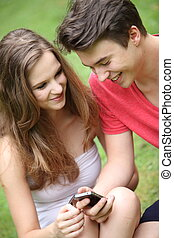 Smiling young teenagers using a mobile - Smiling young...