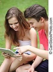 Teenage boy and girl using a tablet-pc - Attractive relaxed...