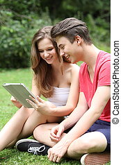 Young teenage friends sharing a tablet-pc - Young teenage...