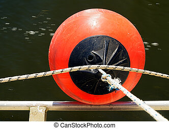 Boat fender and flowing river water - Bright orange.