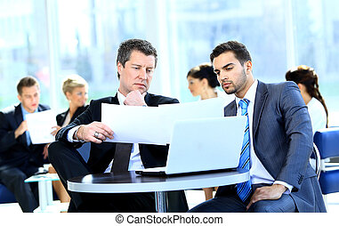 Two businessmen discussing tasks sitting at office table