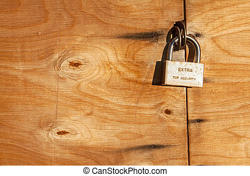 Extra Top Security. Hinged lock on a wooden door.