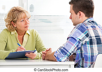 Doctor and patient - Doctor talking to her male patient at...