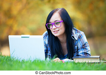 Teen girl with laptop in the park.