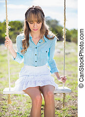 Pensive young model posing while sitting on swing - Pensive...