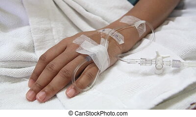 saline drip into patient hand - closeup saline drip into...