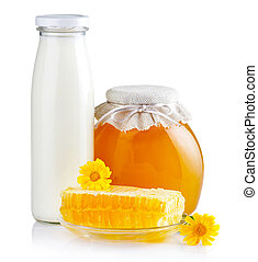 Sweet honey in glass jars with flowers, honeycombs and bottle of milk isolated on white