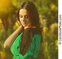 Beautiful romantic woman looking down on sunny summer day...