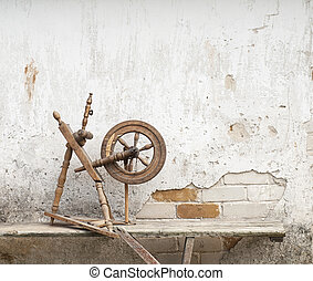 Old spinning wheel - old spinning wheel on the bench, wall...
