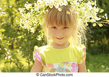 beautiful little girl in a wreath of flowers on the nature
