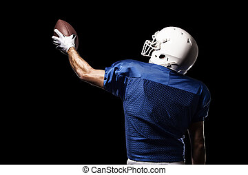 Football Player with a blue uniform celebrating on a Black...
