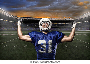 Football Player with a blue uniform celebrating with the...