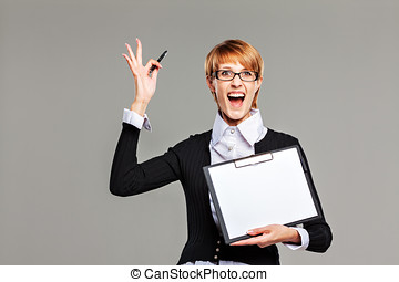 Business woman holding a clipboard with blank paper and...