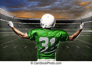 Football Player with a green uniform celebrating with the...