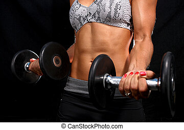 Attractive girl working out in the gym with dumbbells