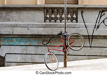 Bicycle Chained to a Post - Red bicycle chained to a post in...