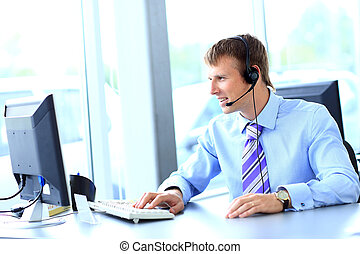 Happy young man working at call center, using headset